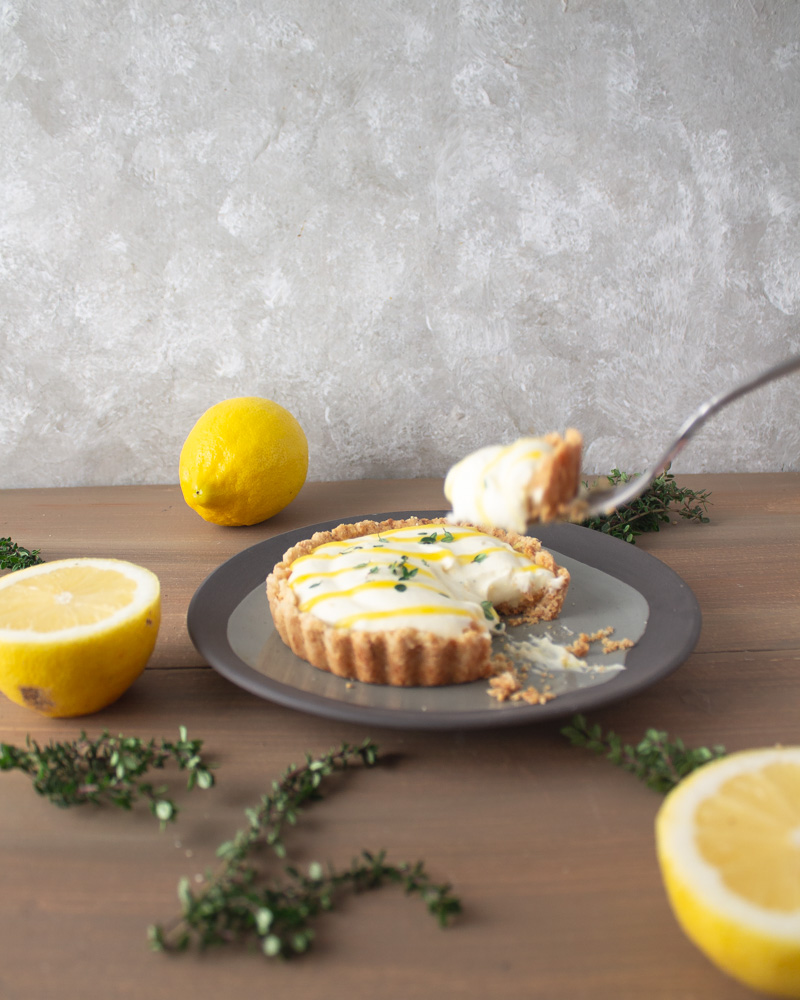 Lemon thyme tart on plate with fork and bite