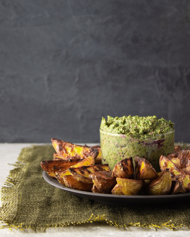 Side view of greens spread with potato wedges