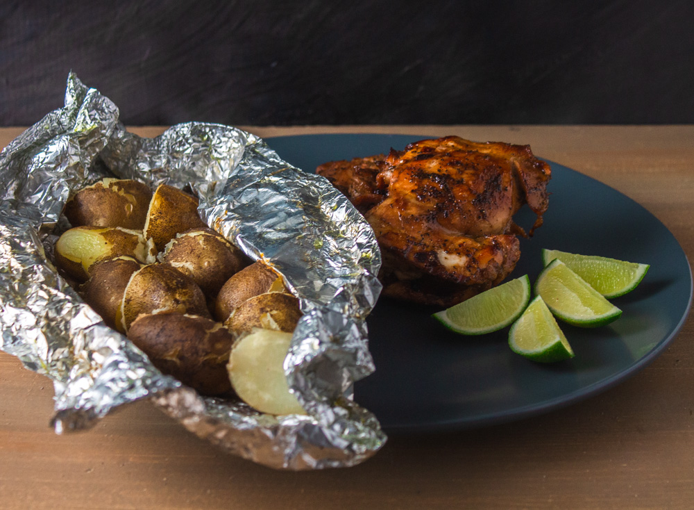 Potatoes in foil on grey plate with chicken and lime wedges