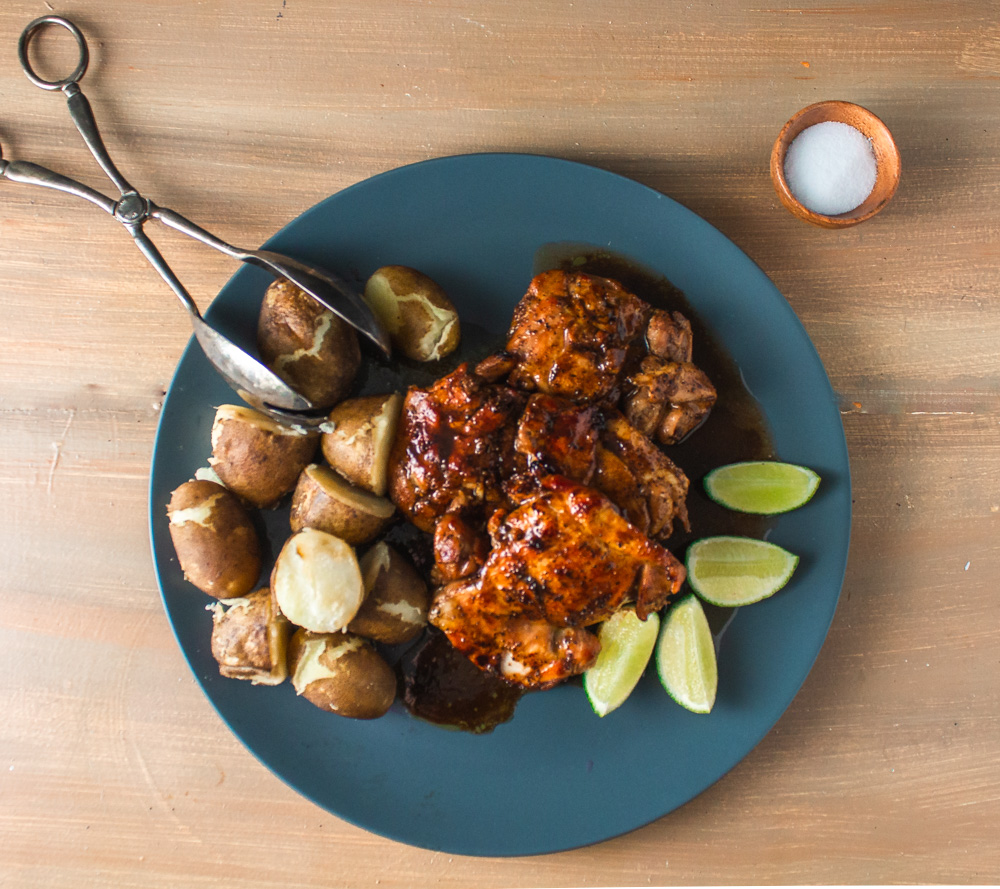 Top view of cooked marinated chicken and potatoes on grey plate with lime wedges