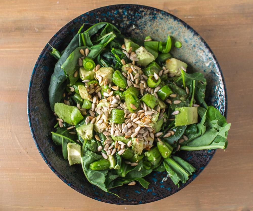 Salad of baby greens, snap peas, and avocado in a dark bowl