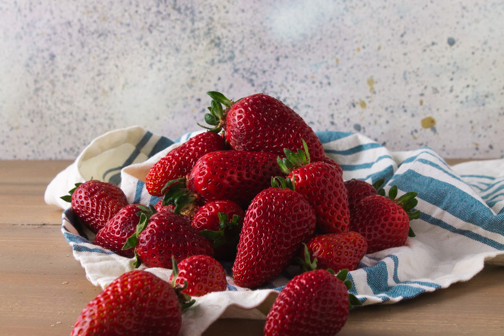 Strawberries on a blue and white cloth.