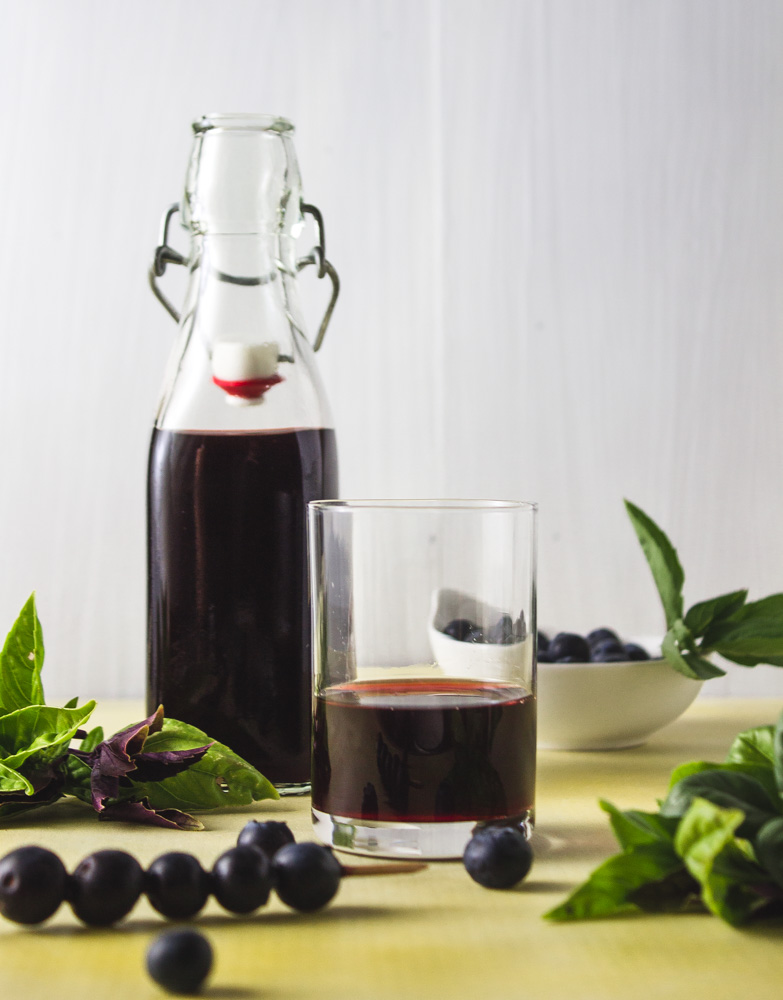 Bottle and glass of shrub with basil and blueberries