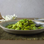 Marinated fava beans on a off-shite plate with bread and cheese in background