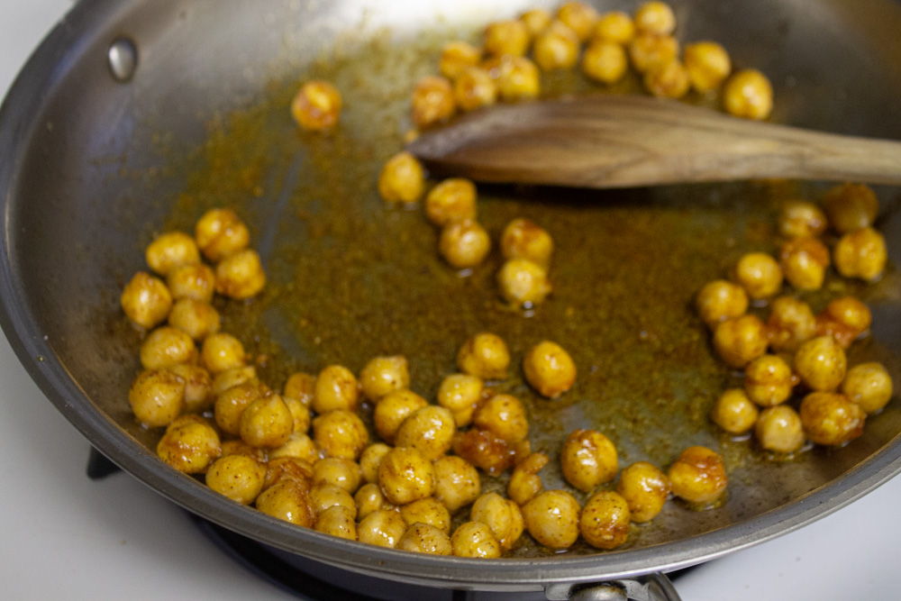 Chickpeas crisping in pan with spices