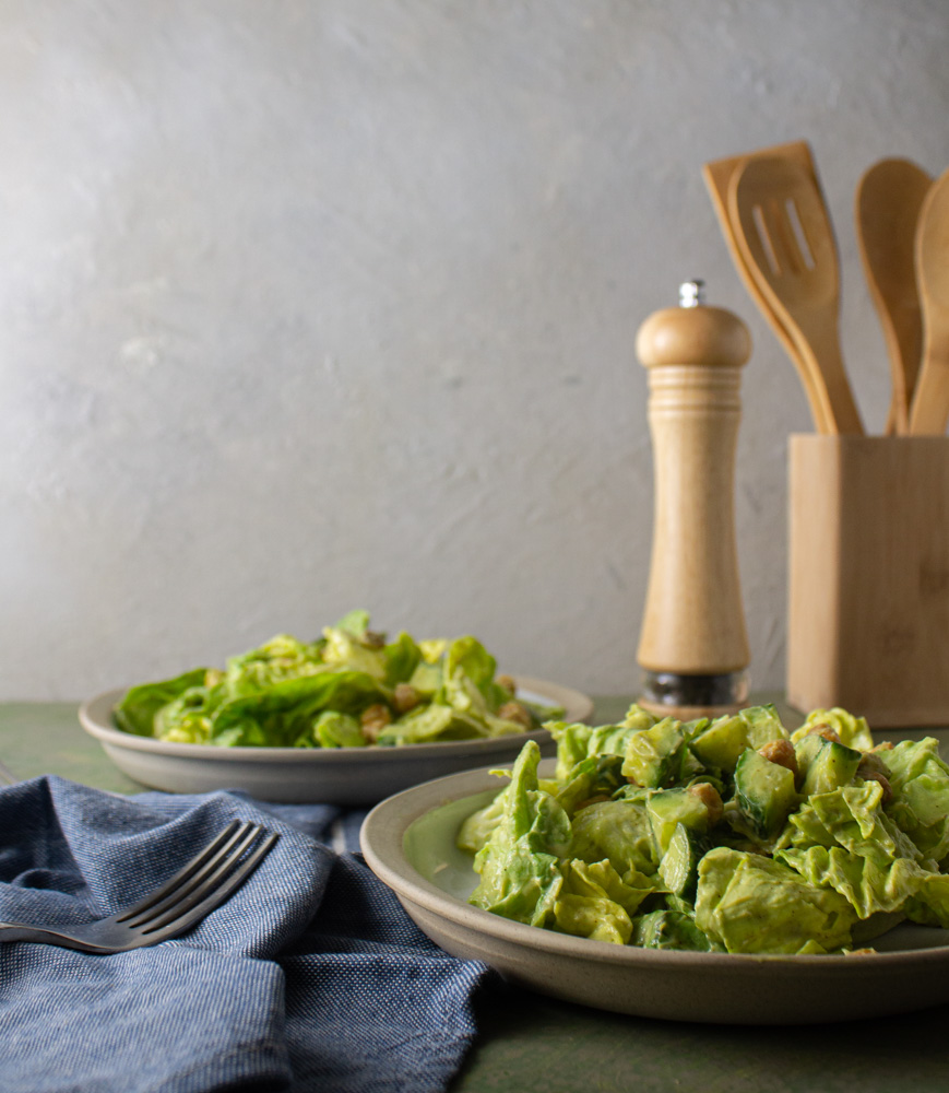 Side view of two salads with wooden utensils in background
