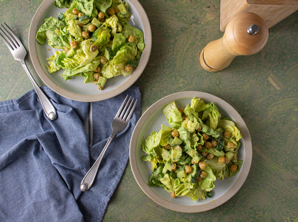Top view of two salads on white plates with blue towel and forks