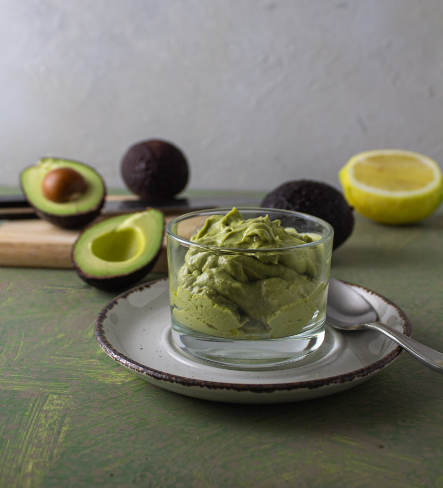 Glass bowl of dressing with avocados and lemons on cutting board