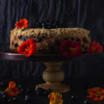 Side view of blueberry buckle on cake stand with nasturiums