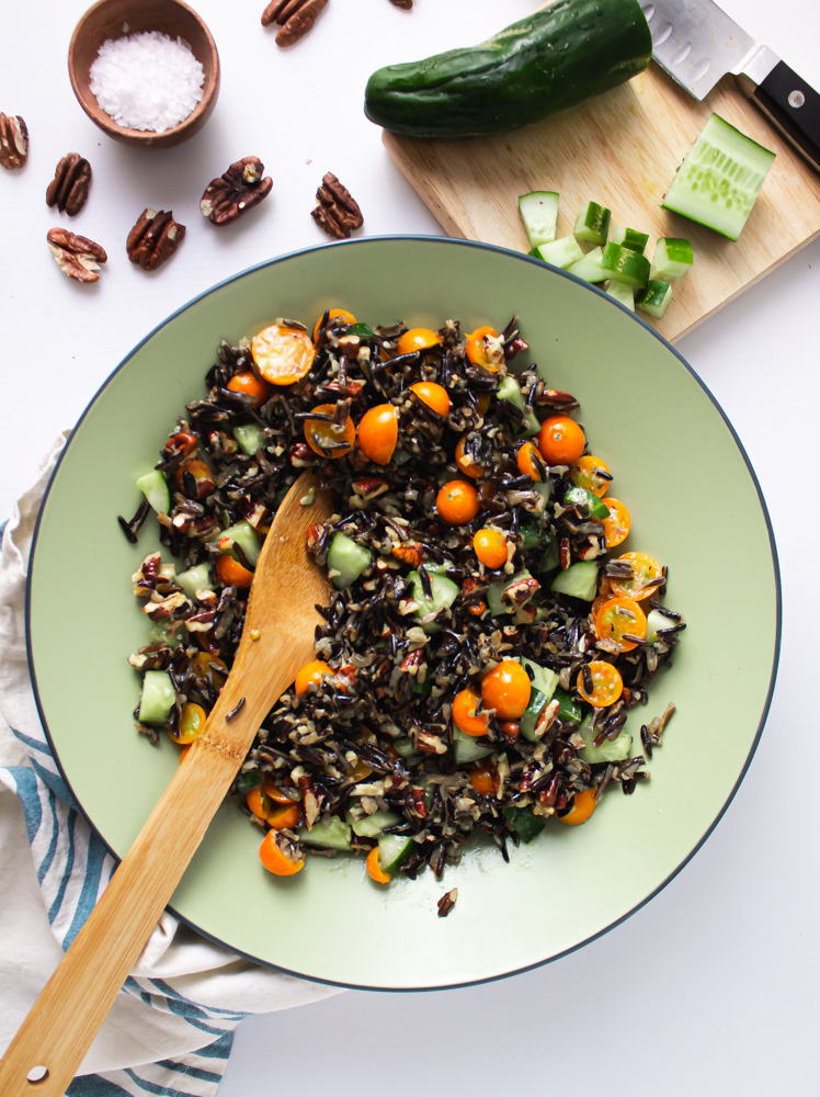Overhead shot of wild rice salad in green bowl with cucumber