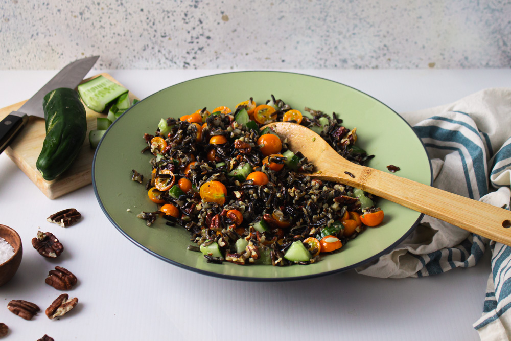 Side angle shot of wild rice salad with cucumber and striped towl