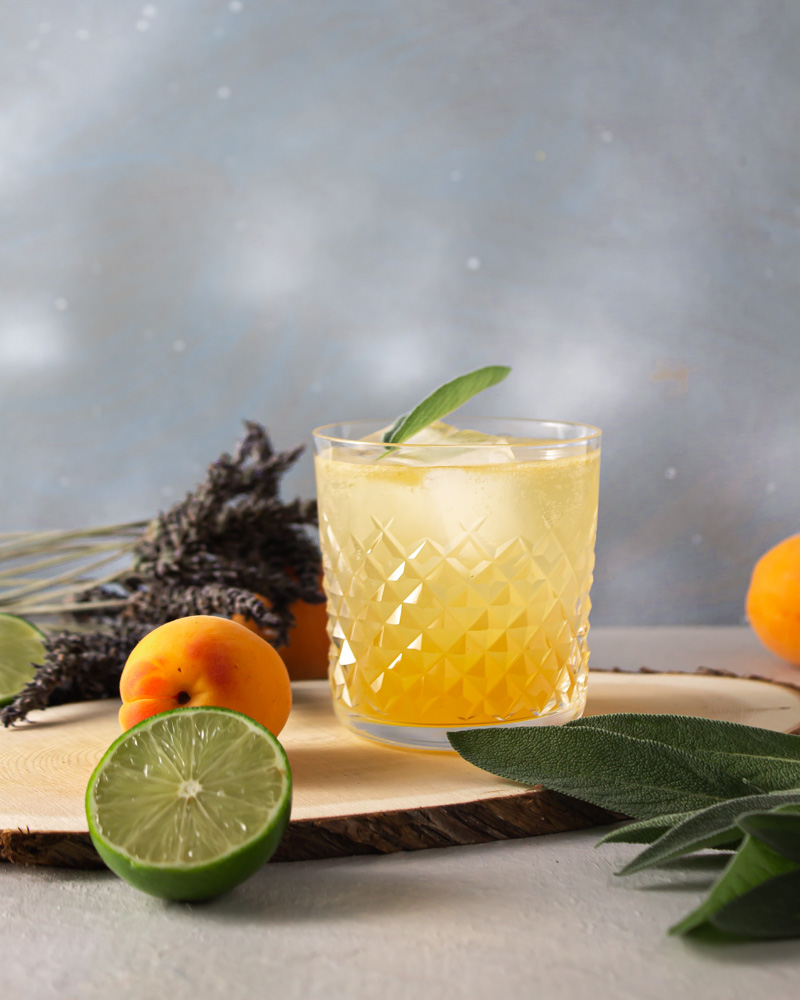 Apricot shrub spritz with fruit and lavender against a blue background