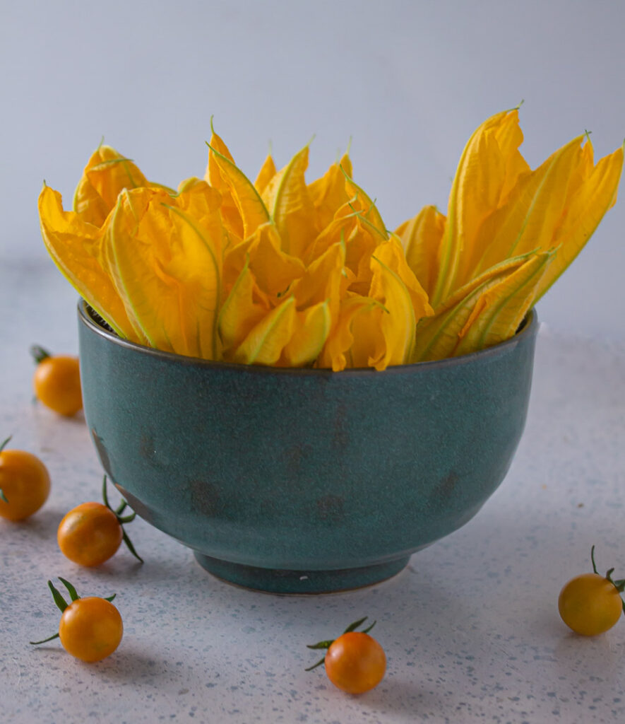 Blue bowl of squash blossoms with sun gold tomatoes scattered