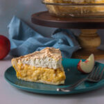Side view slice of stone fruit meringue pie with stand in background