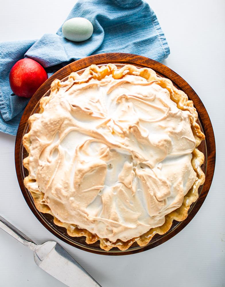 Overhead shot of whole stone fruit meringue pie
