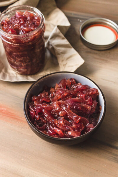 Small bowl and jar of onion jam on a wood table