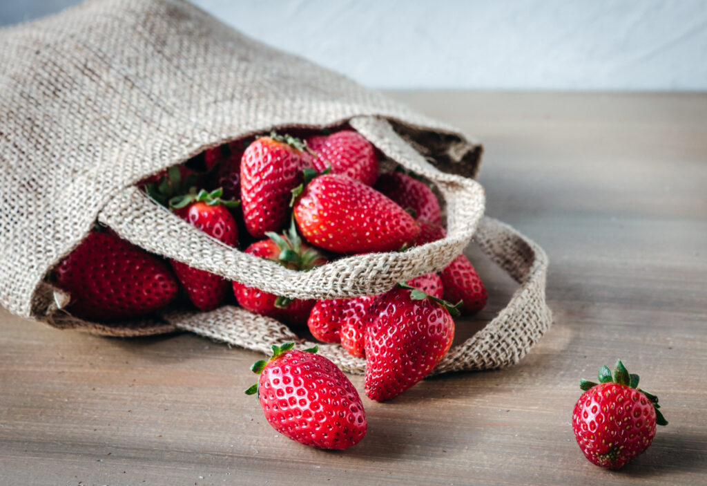 Hemp bag with fresh strawberries spilling out on a wood table