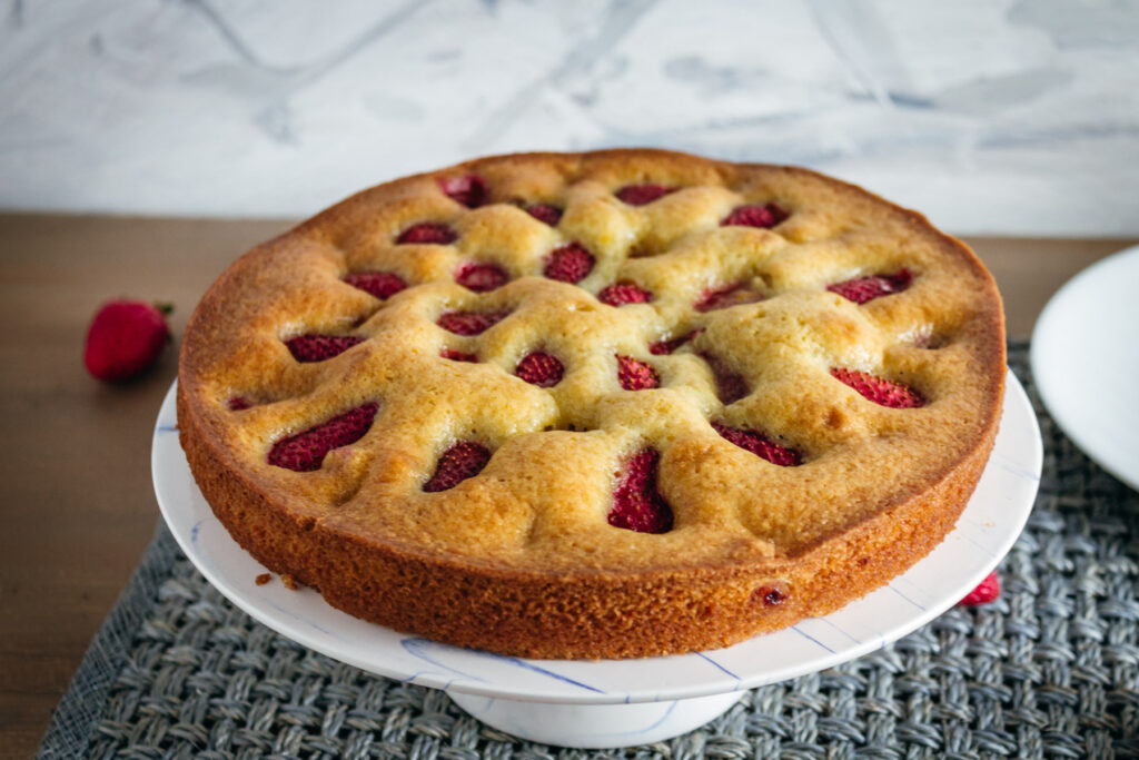 Strawberry olive oil cake on a cake stand.
