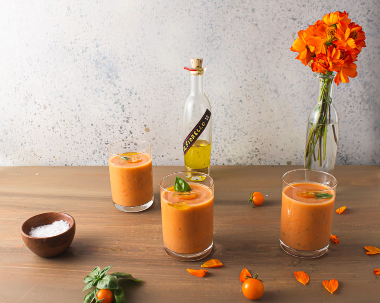 Three glasses of corn tomato gazpacho with flowers on table