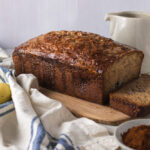 Single slice with remaining loaf of banana and coffee cake with banana and white jug
