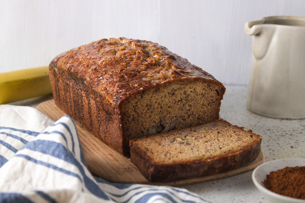 Front view banana and coffee cake with single slice and white jug