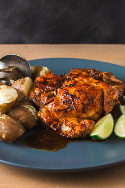 Side view of cooked marinated chicken and potatoes on grey plate with lime wedges
