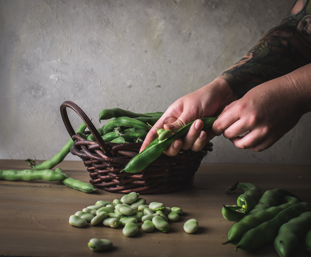 Shelling favas from a basket