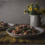 Two plates of farro salad and flowers on a table