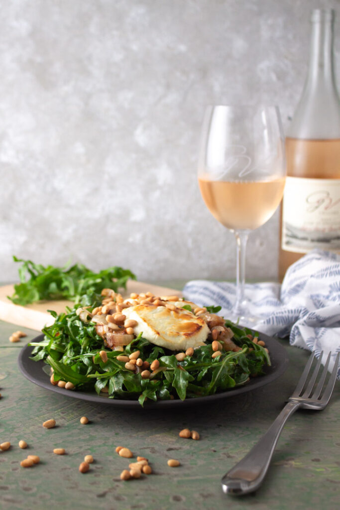 Arugula salad with goat cheese and onions with wine in background