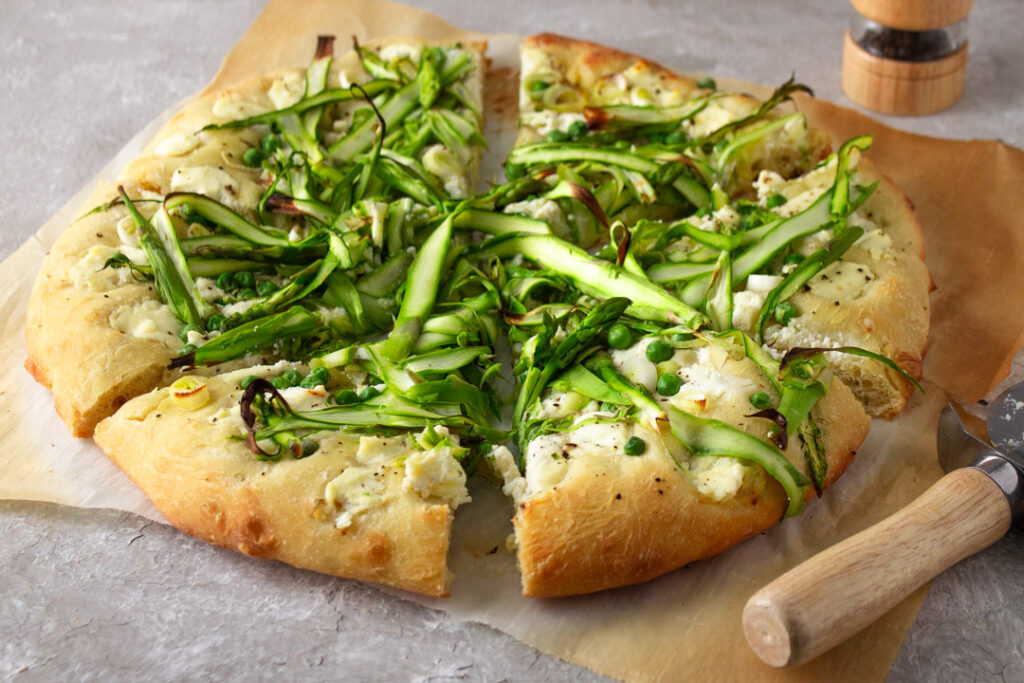 Asparagus and pea pizza on parchment