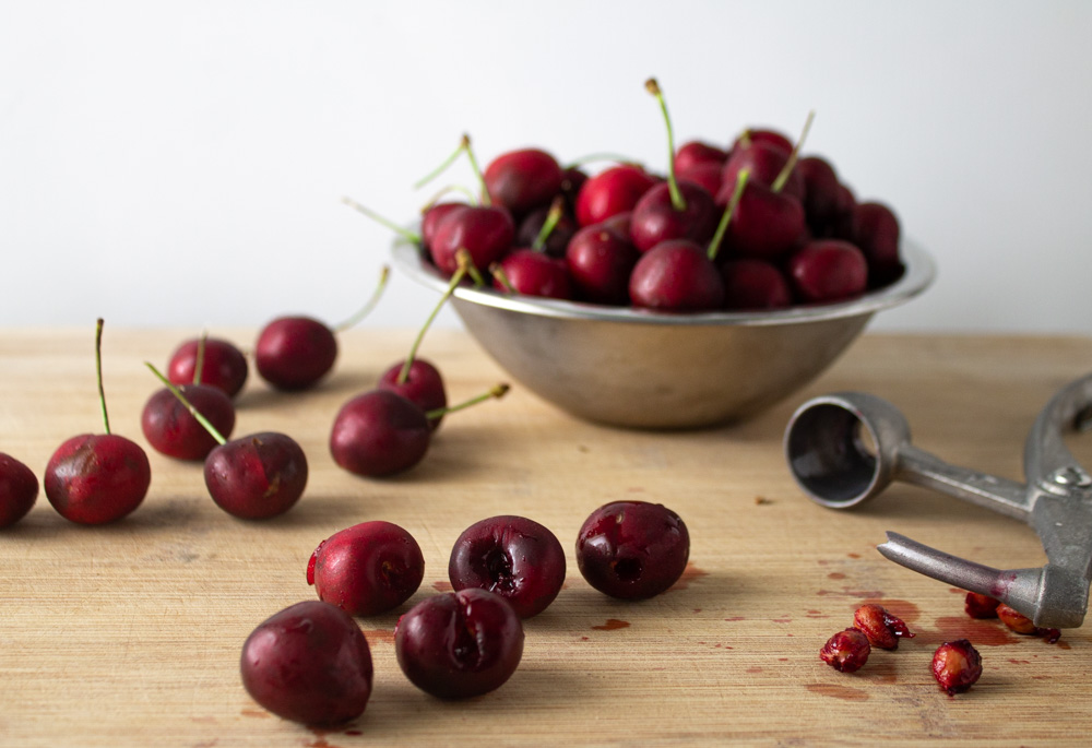 Lots of cherries in a metal bowl and a few pitted on a cutting board