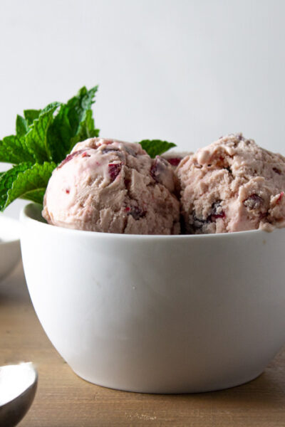 White bowl of cherry mascarpone ice cream with mint sprig