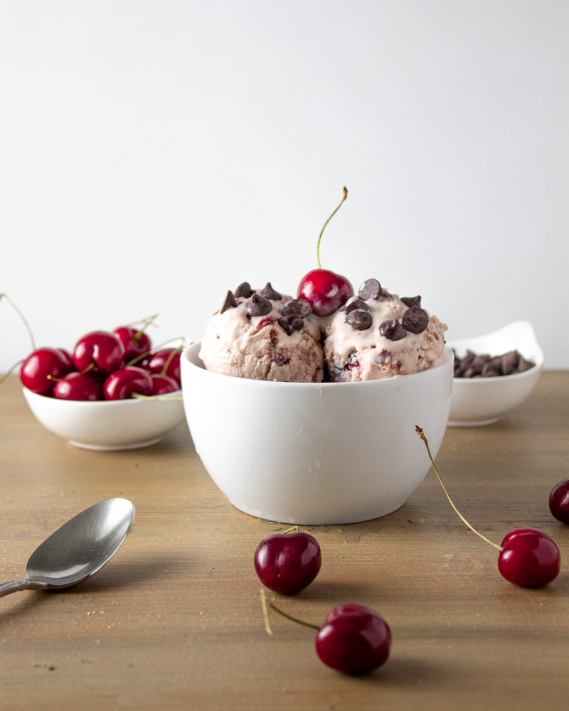 White bowl of ice cream with fresh cherries and chocolate chips