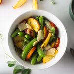 Peach and snap peas salad in white bowl