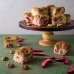 Side view of rhubarb cream cake on cake stand and green background