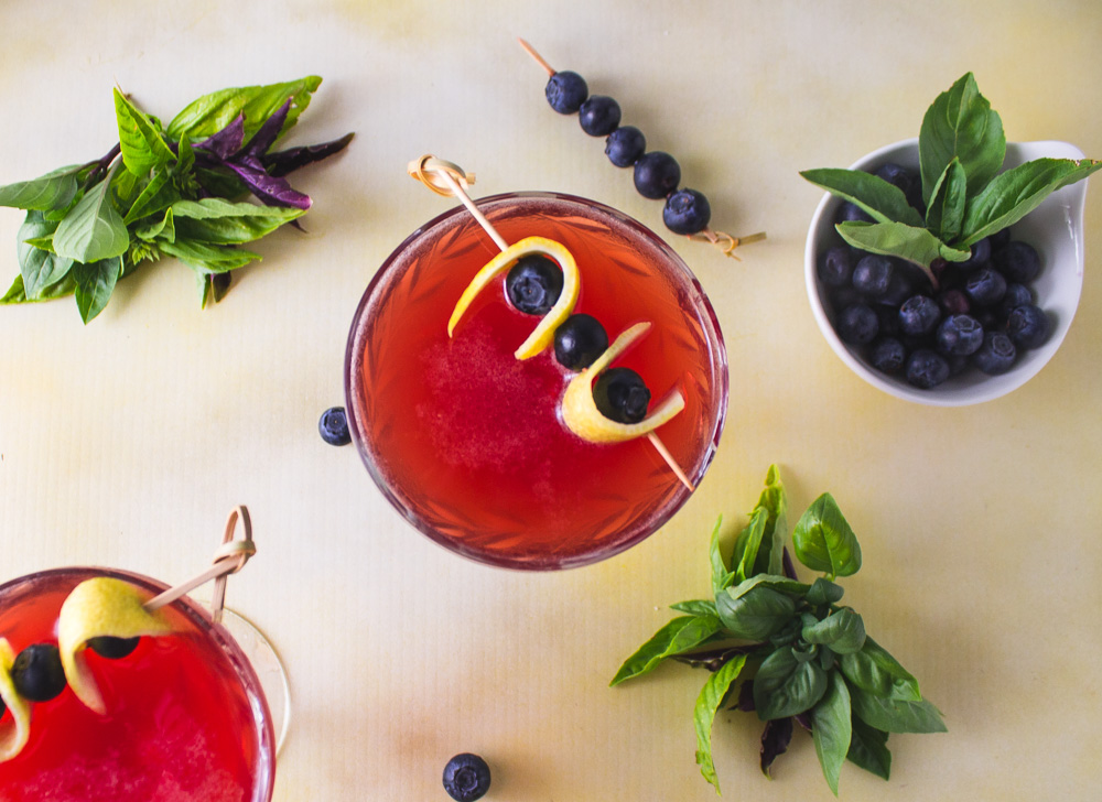 overhead shot of two blueberry basil shrub cocktails with basil and blueberries