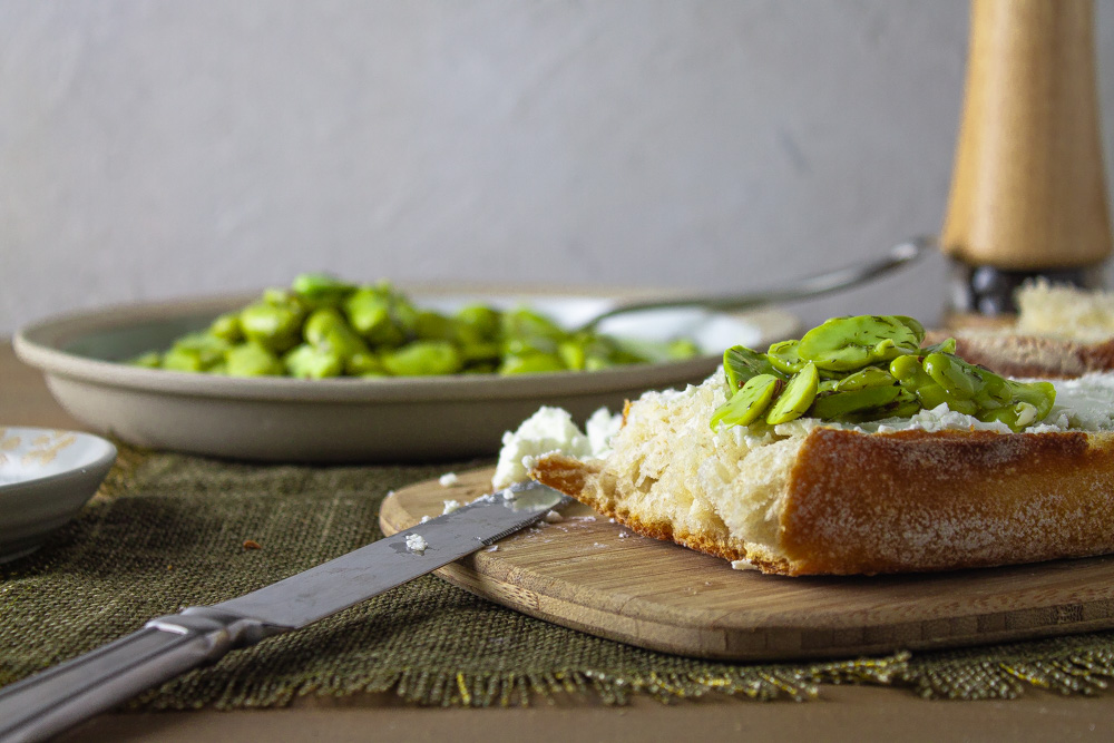 Side view of marinated fava beans on bread with goat cheese