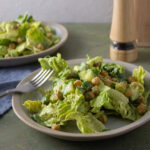 2 salads on off white plates with forks on green background