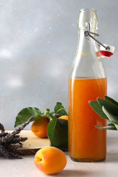 apricot lavender sage shrub in a bottle with lavender apricots and sage on blue background