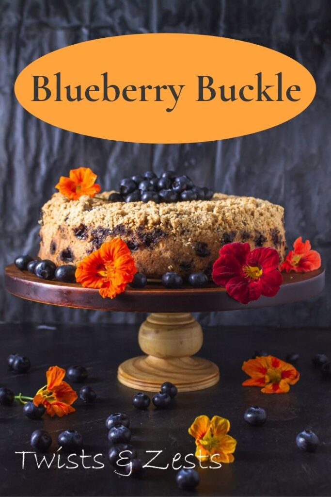 Side view of blue berry buckle on a cake stand with nasturtiums