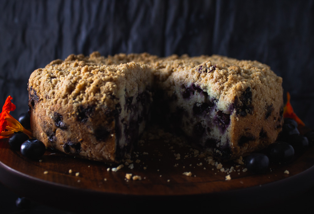 Side view of cut blueberry buckle on stand