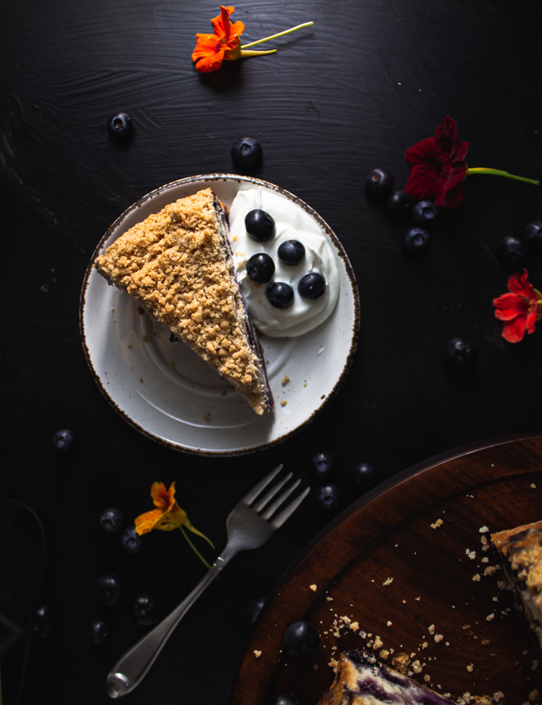 Overhead view of blueberry buckle slice on plate with yogurt