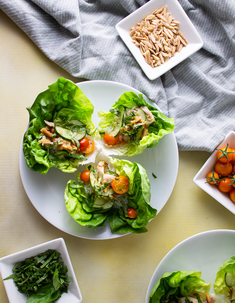 Over head image plates of chicken lettuce wraps with bowls of tomatoes almonds and basil