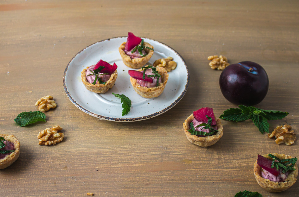 Angle shot of 1 plate of tarts on wood with plum and walnuts