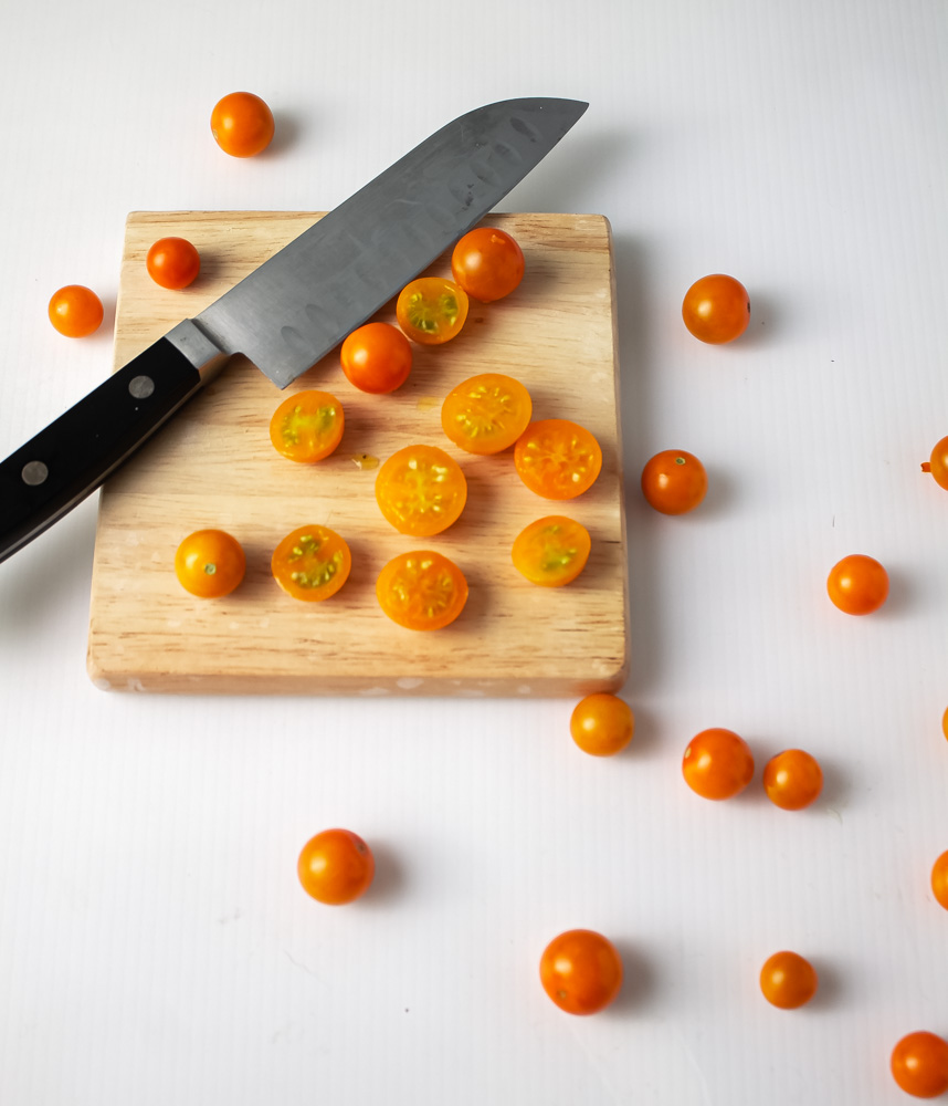 Sungold tomatoes partially cut on white background with knife