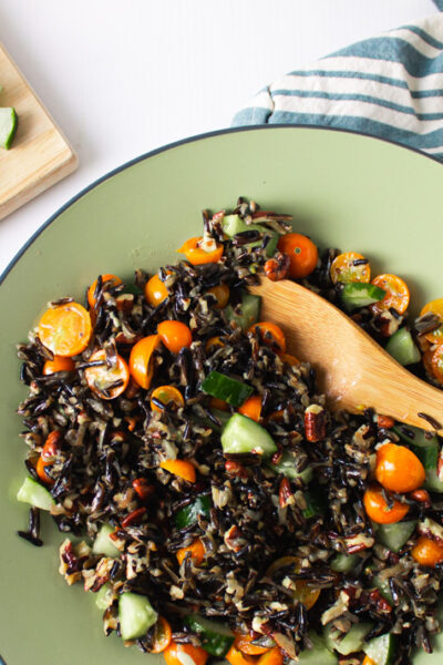 Overhead shot of wild rice salad with cucumber and blue striped towl