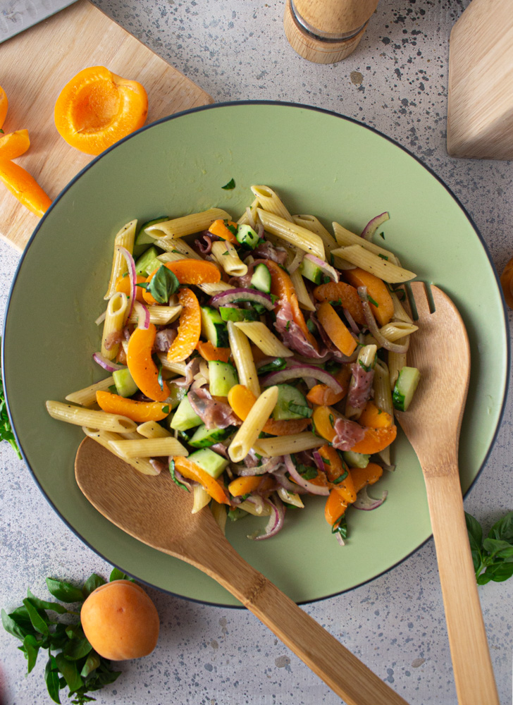 Top view of pasta salad in a green bowl with apricots