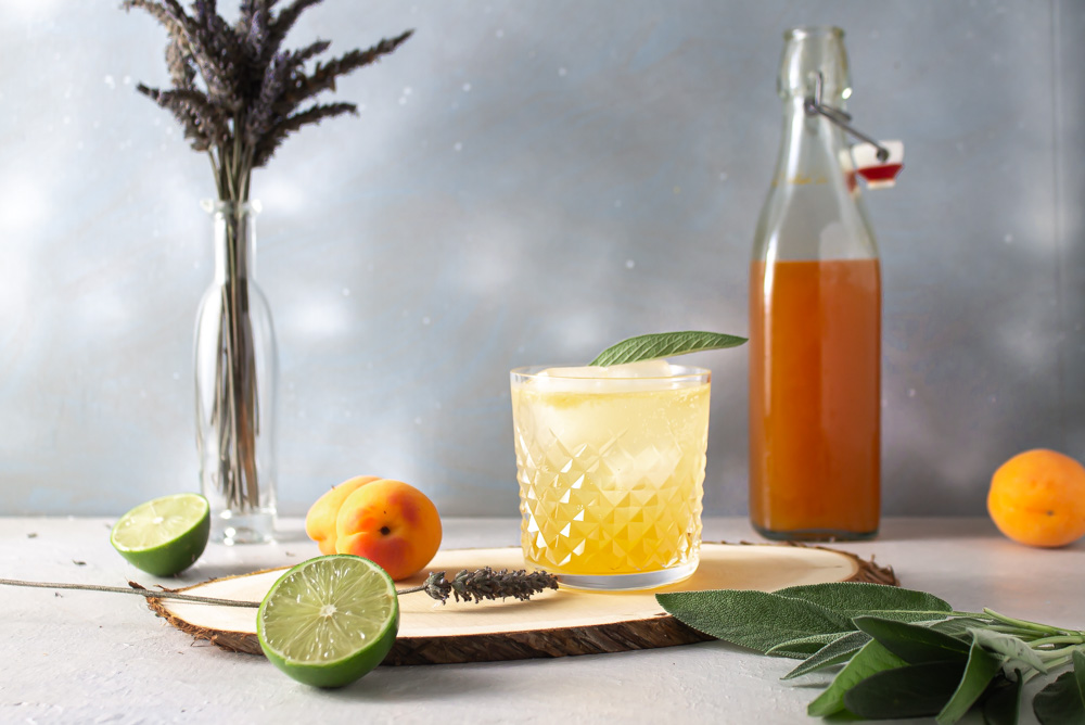 Apricot shrub gin spritz with bottle of shrub and fruit against a blue background