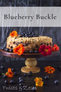 Blueberry buckle on cake stand with flowers