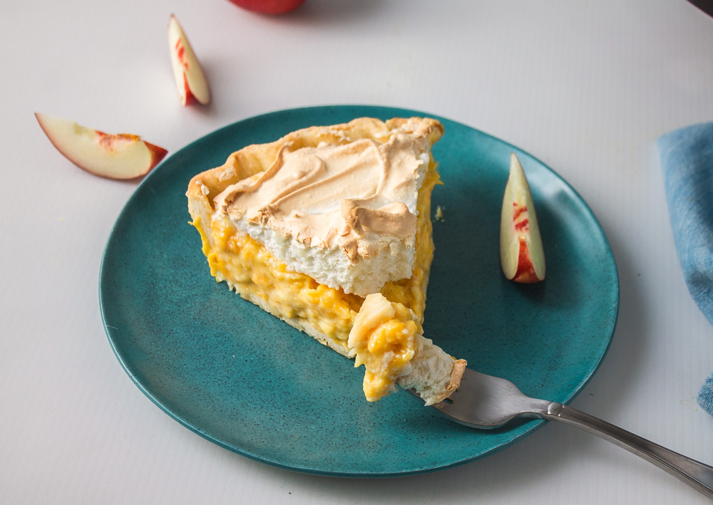 Slice of stone fruit meringue pie with fork ready to take a bite